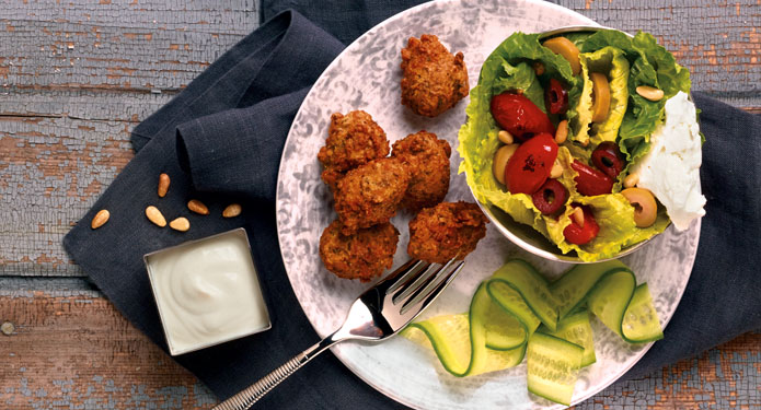 falafel balls on a salad plate with romaine, tomatoes, cucumbers and olives and tahini dressing