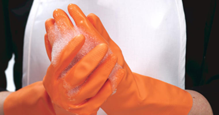 Orange rubber gloves with soap on them