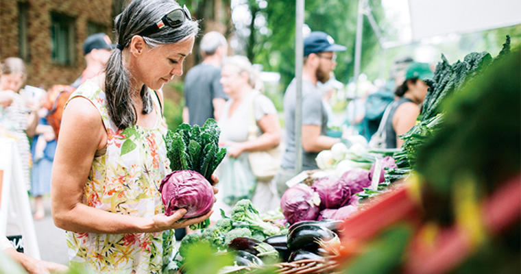 Woman shopping for fresh vegetables at a farmers market