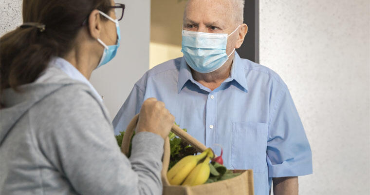 A senior receives a bag of groceries from a healthcare worker