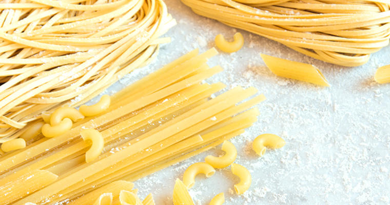 Uncooked yellow pasta noodles on a floured work surface